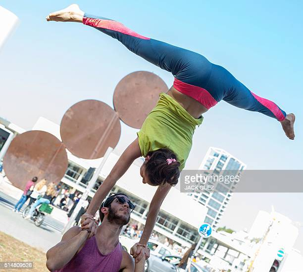 Israelis warmup before taking part in a large acroyoga flashmob on March 11 2016 on Habima Square in the coastal city of Tel Aviv Some 150 people...