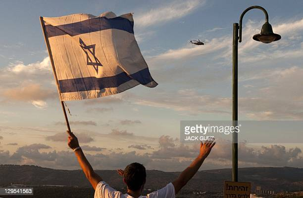 Israelis wave flags as helicopters transporting Israeli soldier Gilad Shalit and his family prepare to land at their home town of Mitzpe Hila...