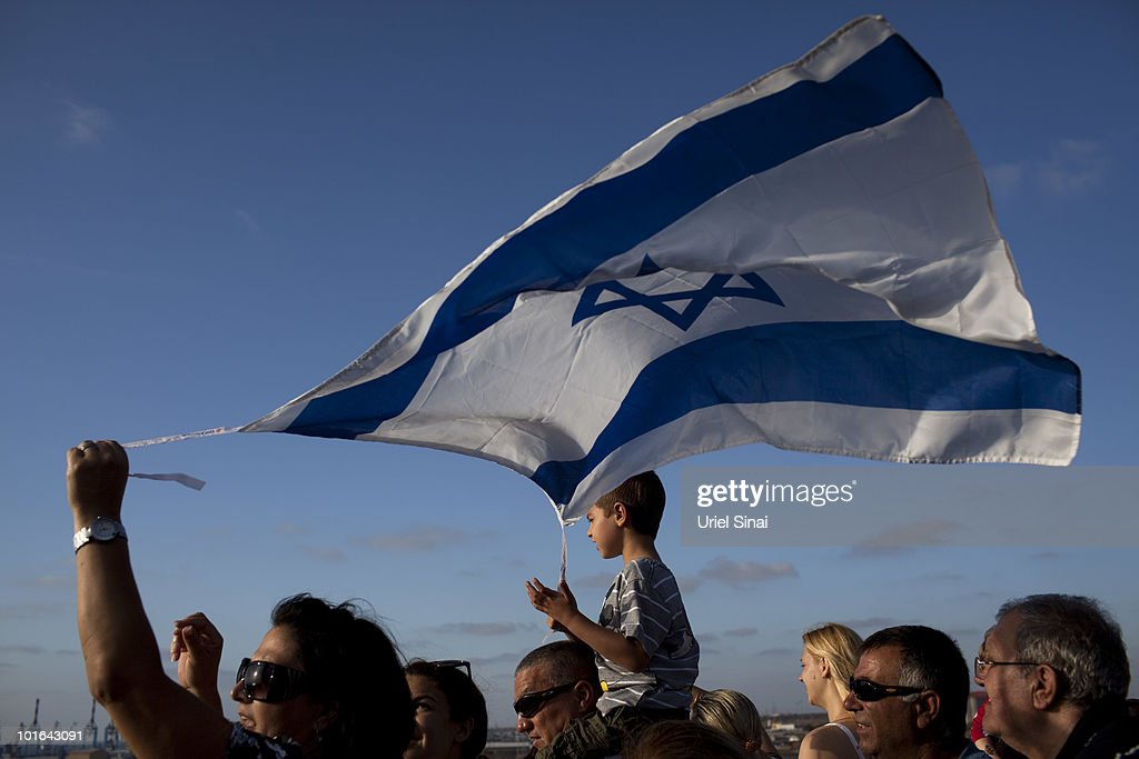 Israelis wave their national flag as the Rachel Corrie aid ship enters the military port of Ashdod in southern Israel after it was intercepted by the Israeli Navy on June 5, 2010, in Ashdod, Israel. Israel, which has faced international criticism over the deadly May 31 raid on a ship carrying humanitarian aid to the Gaza Strip, seized the Rachel Corrie today preventing it from reaching Gaza.