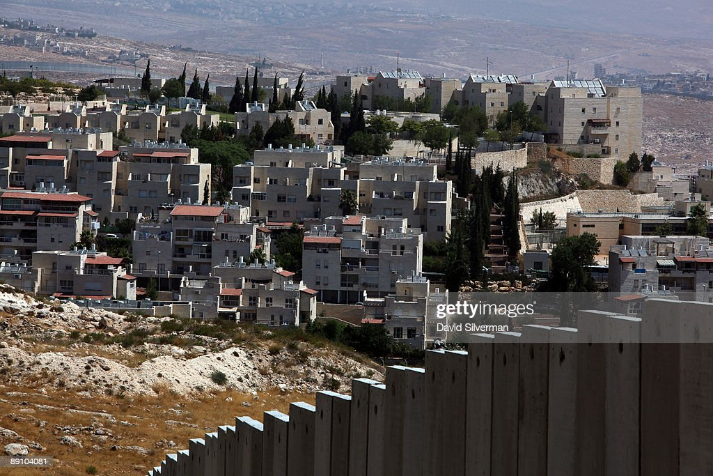 Israel's controversial West Bank barrier seperates the Jewish neighbourhood of Pisgat Zeev from the Palestinian refugee camp of Shuafat July 19 2009...