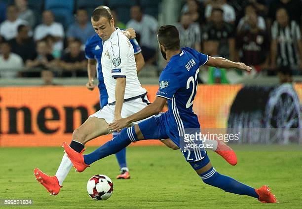 Israel's defender Ben Bitton tries to tackle Italy's defender Luca Antonelli during their World Cup 2018 qualification match between Israel and Italy...