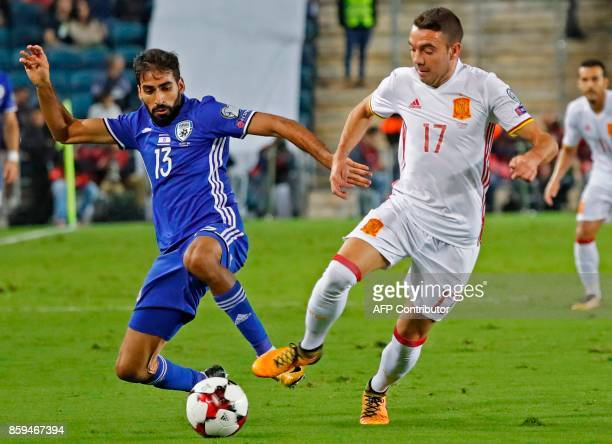 Israel's defender Ofir Davidadza vies for the ball with Spain's forward Iago Aspas during the Russia 2018 FIFA World Cup European Group G qualifying...