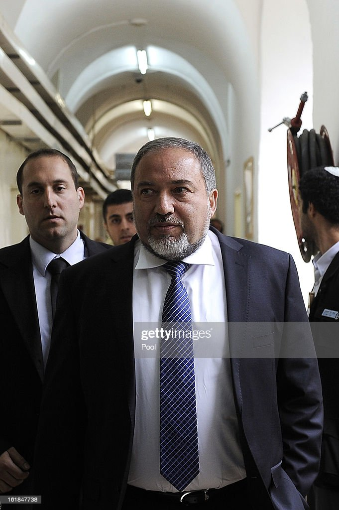 Israel's former Foreign Minister Avigdor Lieberman (C) arrives for the opening hearing of his trial in which is he is facing charges of fraud and breach of trust, at Jerusalem Magistrates Court on February 17, 2013 in Jerusalem, Israel. Concerning incidents which took place more than a decade ago, Lieberman is accused of trying to advance the career of a former diplomat who relayed information to him about a since closed criminal investigation into his business dealings. Lieberman pleaded not guilty on all counts, expressing confidence that he will be cleared of all charges so that he may resume his role as Foreign Minister.