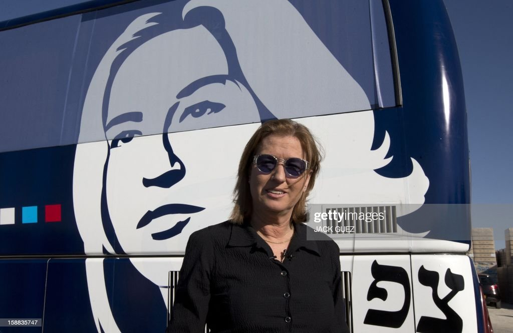Israel's former foreign minister Tzipi Livni and chairman of a new party called The Movement poses for a photo in front of her tour bus after her visit to a factory of glass bottles during a campaign rally in the southern city of Yeruham, south of Beer Sheva, on December 31, 2012. Livni announced her return at the helm of The Movement party, nearly seven months after she stepped aside following a primary defeat. AFP PHOTO / JACK GUEZ