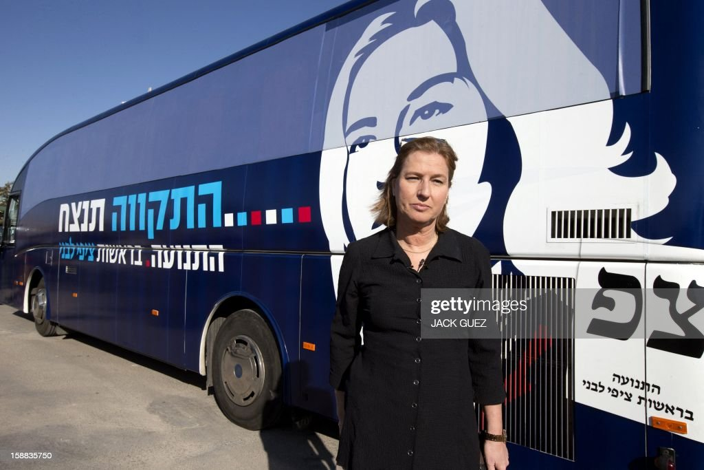 Israel's former foreign minister Tzipi Livni and chairman of a new party called The Movement poses for a photo in front of her tour bus after her visit to a factory of glass bottles during a campaign rally in the southern city of Yeruham, south of Beer Sheva, on December 31, 2012. Livni announced her return at the helm of The Movement party, nearly seven months after she stepped aside following a primary defeat.