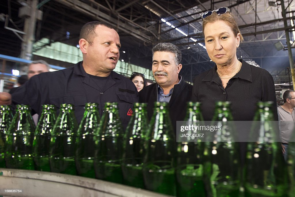 Israel's former foreign minister Tzipi Livni and chairman of a new party called The Movement, looks at the line as she visits a factory of glass bottles during her campaign rally in the southern city of Yeruham, south of Beer Sheva, on December 31, 2012. Livni announced her return at the helm of The Movement party, nearly seven months after she stepped aside following a primary defeat.
