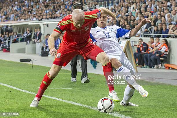 Israel's forward Tal Ben Haim fights for the ball with Wales' defender James Collins during the Euro 2016 qualifying football match between Israel...