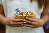 Girl's hands holding pita with falafel and an Israeli flag