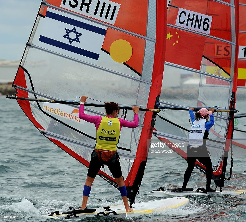 Israel's Lee Korzits (L) and China's Wang Ning (R) round a mark in the first Gold Fleet race in the