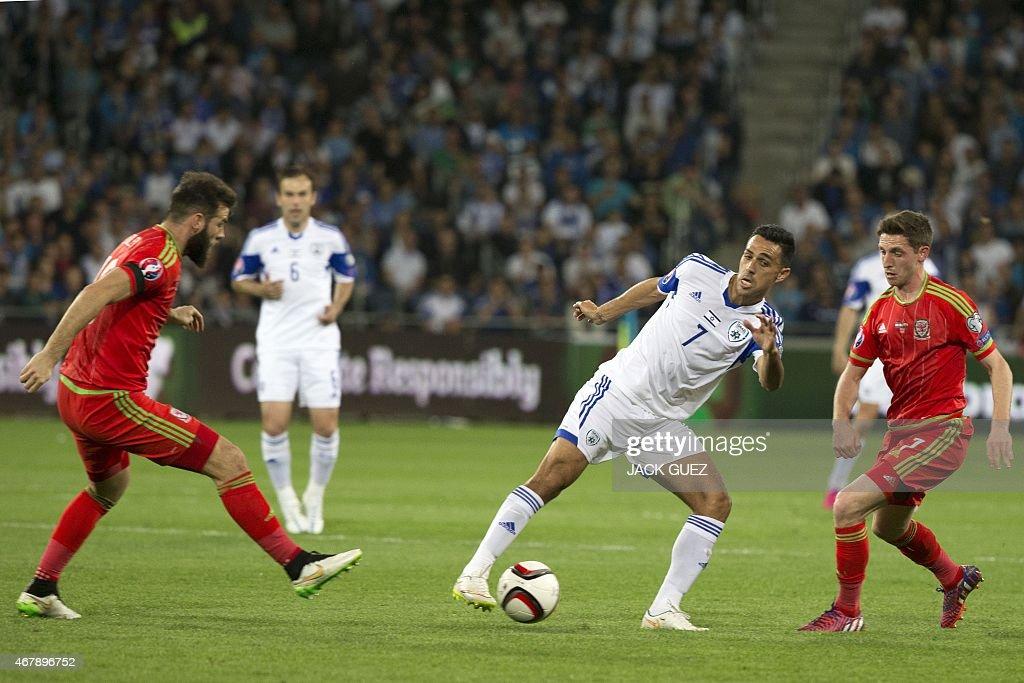 Israel's midfielder Eran Zahavi controls the ball as he is defended by Wales' midfielder Joe Allen and Joe Ledley during the Euro 2016 qualifying...
