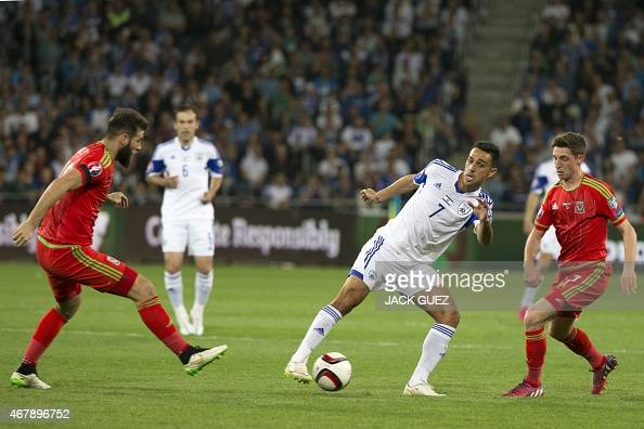 Israel's midfielder Eran Zahavi controls the ball as he is defended by Wales' midfielder Joe Allen and Joe Ledley during the Euro 2016 qualifying...