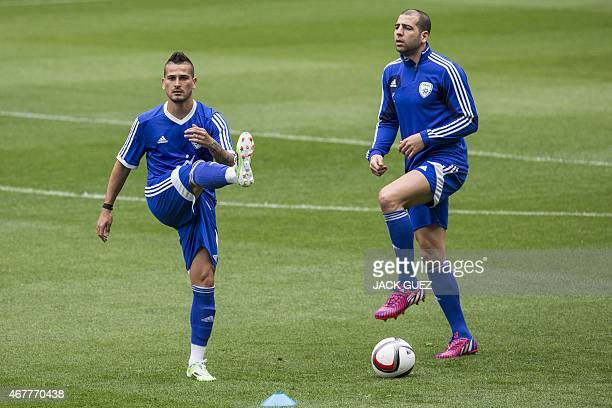 Israels midfielder Maor Buzaglo and defender Tal ben Haim take part in a training session at the Sammy Ofer Stadium in the Israeli coastal city of...