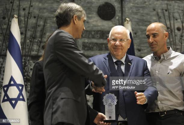 Israel's President Reuven Rivlin presents the Shield of Honour prize to Eli Ohana the Chairman of Beitar Jerusalem football club as he stands next to...