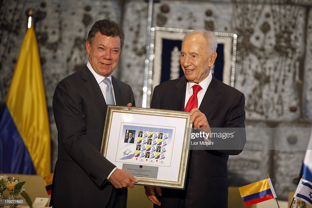 Israel's President Shimon Peres, (R) presents a gift to Colombia's President Juan Manuel Santos after a meeting at the president's residence on June 10, 2013 in Jerusalem, Israel. The Colombian President is on a three-day visit to Israel, where he is expected to meet with senior Israeli officials to discuss regional and bilateral issues.