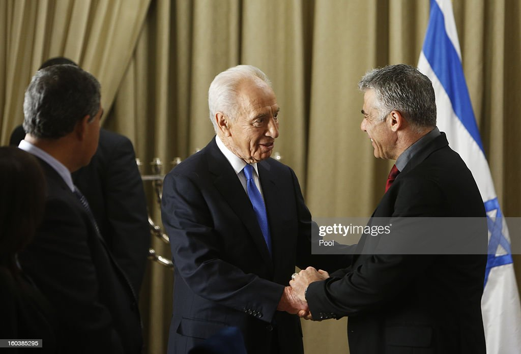 Israel's President Shimon Peres (L) shakes hands with Yair Lapid, leader of the Yesh Atid (There's a Future) party, speaks during their meeting on January 30, 2013 in Jerusalem, Israel. President Shimon Peres today formally began a period of consultation with the various parties to select the MP most able to put together the country's next ruling coalition, with incumbent Prime Minister Benjamin Netanyahu the favourite to assemble the coalition.
