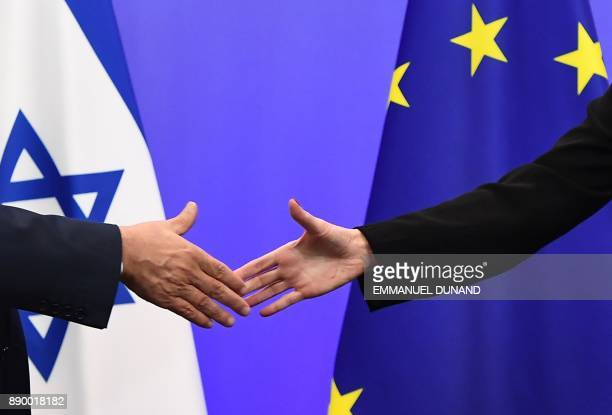 Israel's Prime Minister Benjamin Netanyahu and EU foreign policy chief Federica Mogherini shake hands during a press conference at the European...