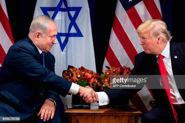 TOPSHOT Israel's Prime Minister Benjamin Netanyahu and US President Donald Trump shake hands before a meeting at the Palace Hotel during the 72nd...