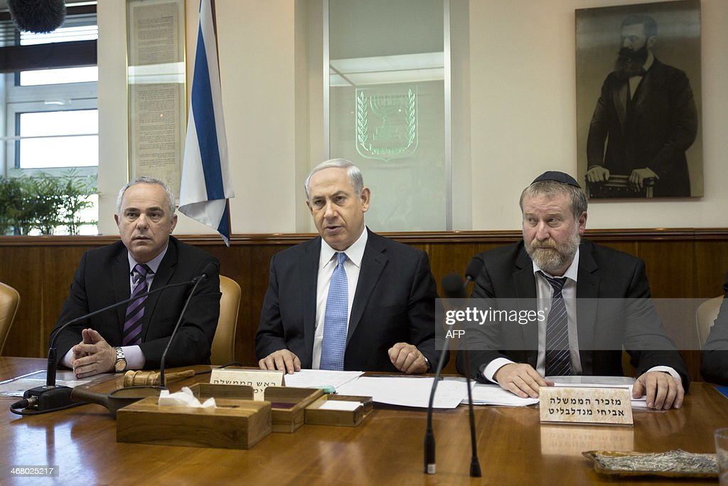 Israel's Prime Minister Benjamin Netanyahu (C) chairs the weekly cabinet meeting near Cabinet Secretary Avichai Mandelblitt (R) and Minister of Intelligence Yuval Steinitz (L) on February 9, 2014 in Jerusalem. AFP PHOTO / POOL / SEBASTIAN SCHEINER