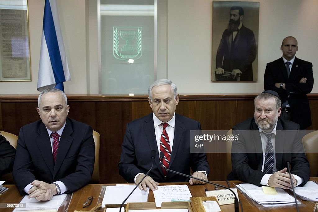 Israel's Prime Minister Benjamin Netanyahu chairs the weekly cabinet meeting near Cabinet Secretary Avichai Mandelblitt (R) and Minister of Intelligence Yuval Steinitz (L) on February 16, 2014 in Jerusalem.