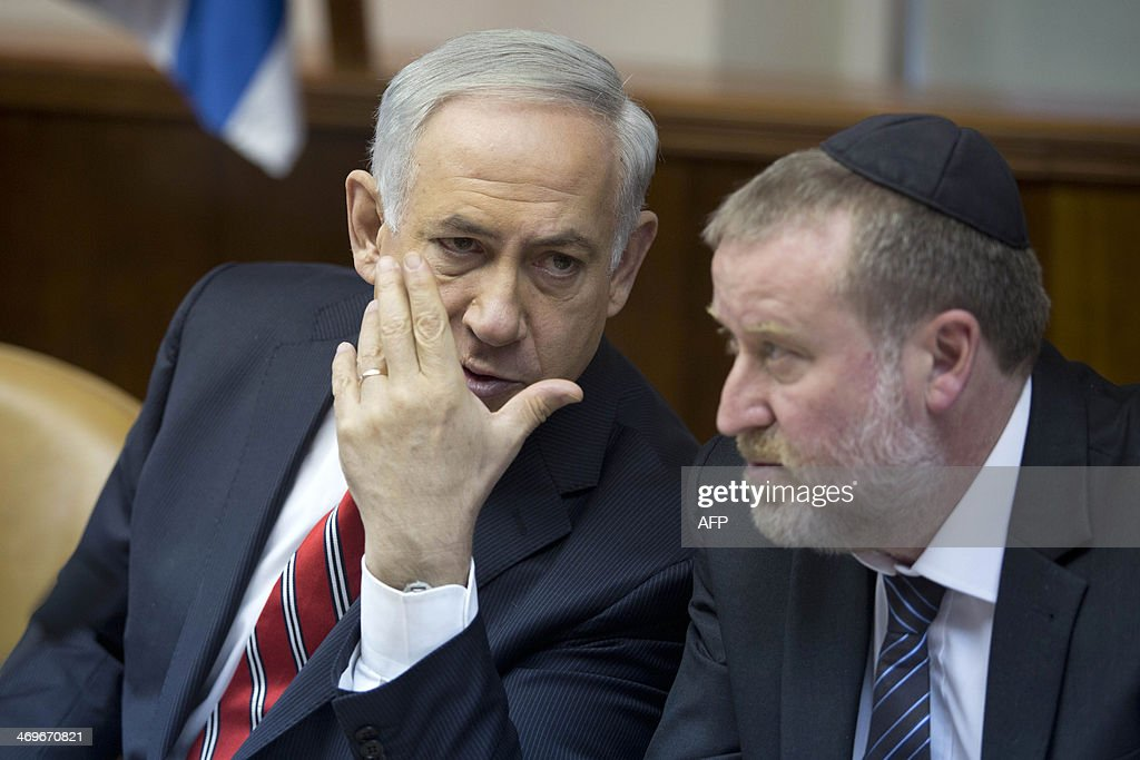 Israel's Prime Minister Benjamin Netanyahu talks with Minister of Intelligence Yuval Steinitz (R) during the weekly cabinet meeting on February 16, 2014 in Jerusalem.