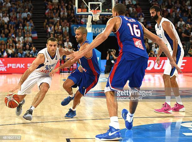 Israel's Raviv Limonad vies with France's Tony Parker and France's Rudy Gobert during the group A qualification basketball match between France and...