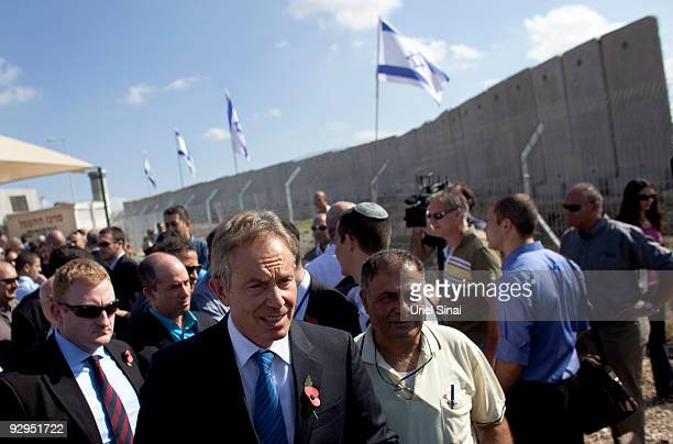 Israel's separation wall is seen in the background as Quartet Middle East envoy Tony Blair takes part in a ribbon cutting ceremony of the Jalama...