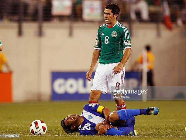 Isreal Castro of Mexico looks on as Carlos Ruiz of Guatemala hold his knee in pain during the 2011 Gold Cup Quarterfinals on June 18 2011 at the New...