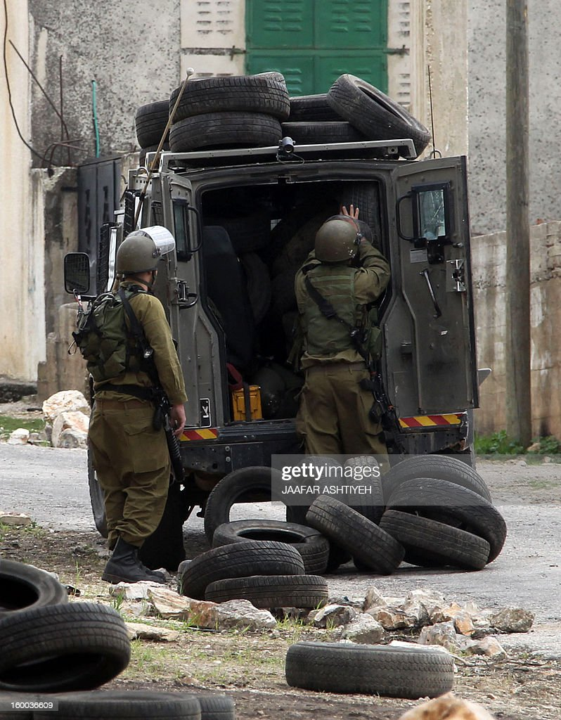 Isreali soldiers load a truck with tyres during a protest of Palestinians against the expropriation of Palestinian land by Israel on January 25, 2013 in the village of Kafr Qadum, near Nablus, in the occupied West Bank. AFP PHOTO/JAAFAR ASHTIYEH