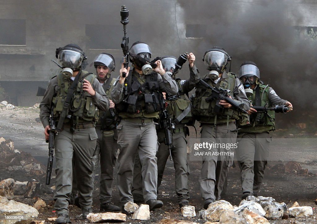 Isreali soldiers walk wearing gas masks during a protest of Palestinians against the expropriation of Palestinian land by Israel on January 25, 2013 in the village of Kafr Qadum, near Nablus, in the occupied West Bank.