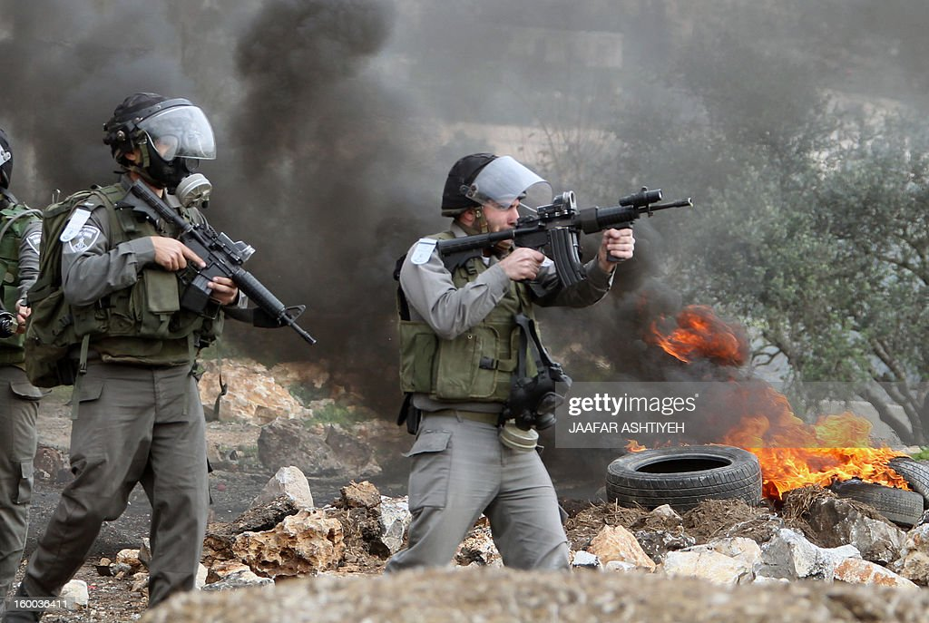 Isreali soldiers wearing gas masks point towards Palestinians during a protest against the expropriation of Palestinian land by Israel on January 25, 2013 in the village of Kafr Qadum, near Nablus, in the occupied West Bank.