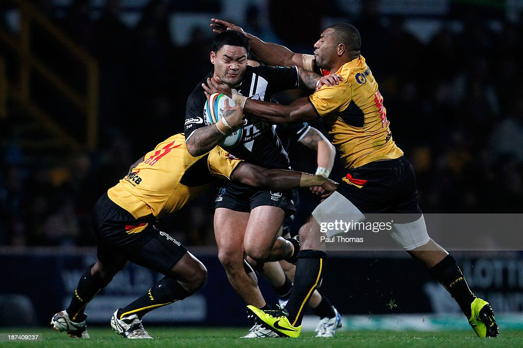 Issac Luke (C) of New Zealand is tackled by Jason Tali (R) and Jessie Joe Nandye of Papua New Guinea during the Rugby League World Cup Group B match at Headingley Stadium on November 8, 2013 in Leeds, England.