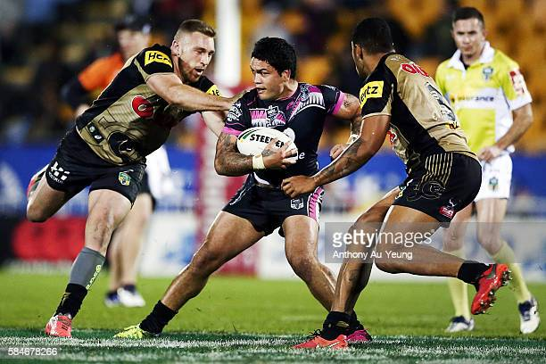 Issac Luke of the Warriors makes a run against Bryce Cartwright and Waqa Blake of the Panthers during the round 21 NRL match between the New Zealand...