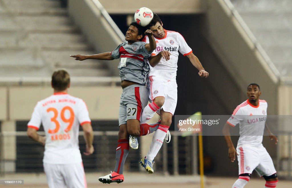 Issiar Dia (L) of Lekhwiya jumps for a header with Javier Martinez of Muenchen during the international friendly match between Lekhwiya Sports Club and FC Bayern Muenchen at Khalifa International Stadium on January 5, 2013 in Doha, Qatar.