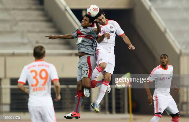 Issiar Dia of Lekhwiya jumps for a header with Javier Martinez of Muenchen during the international friendly match between Lekhwiya Sports Club and...