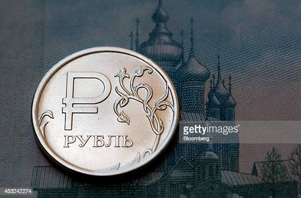 A 2014 issue Russian one ruble coin sits on a banknote in this arranged photograph in Moscow Russia on Tuesday Aug 5 2014 Russian government bonds...
