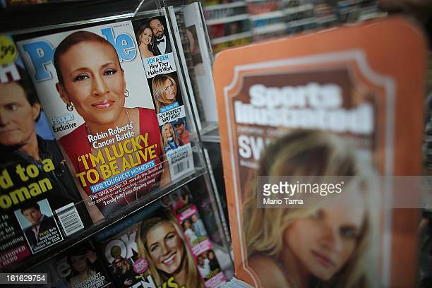 Issues of People magazine are displayed next to a Sports Illlustrated advertisement at a newsstand in Manhattan on February 13 2013 in New York City...