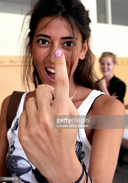 A Turkish woman shows her marked finger to photographers after casting her vote for Turkey's general elections in a polling station in Istanbul 22...