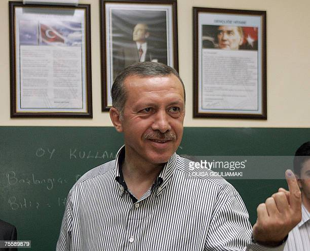 Turkey's Prime Minister Recep Tayyip Erdogan shows his inkmarked finger after casting his vote in legislative elections at a polling station in a...