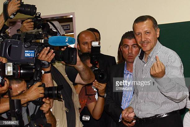 Turkish Prime Minister Recep Tayyip Erdogan shows his inkmarked finger after voting at a polling station in Istanbul 22 July 2007 Voters thronged...