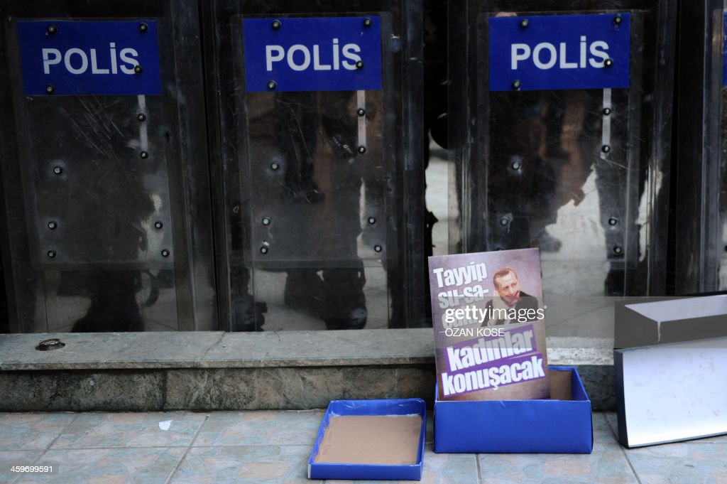 Istanbul women solidarity members leave shoe boxes and picture of Turkish Prime Minister Recep Tayyip Erdogan with slogan 'Tayyip will stop speaking, women will do' next to riot policeshields read during an anti government protest on December 29, 2013 in Istanbul against corruption and the Government. Turkish Prime Minister Recep Tayyip Erdogan lashed out at the judiciary as he tried to tamp down a corruption probe that has shaken his government and sparked a new wave of anti-government protests. The conservative prime minister, who has dug in his heels over the crisis that has led to the resignation of three ministers, went again on the attack during a speech in the southern city of Manisa.