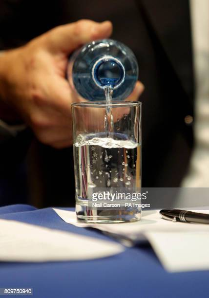 Istvan Szekely of the European Commission pours water into a glass with the EU logo on during a press conference on the progress of Irelands Fourth...