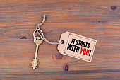 Key and a note on a wooden table with text - It Starts With You