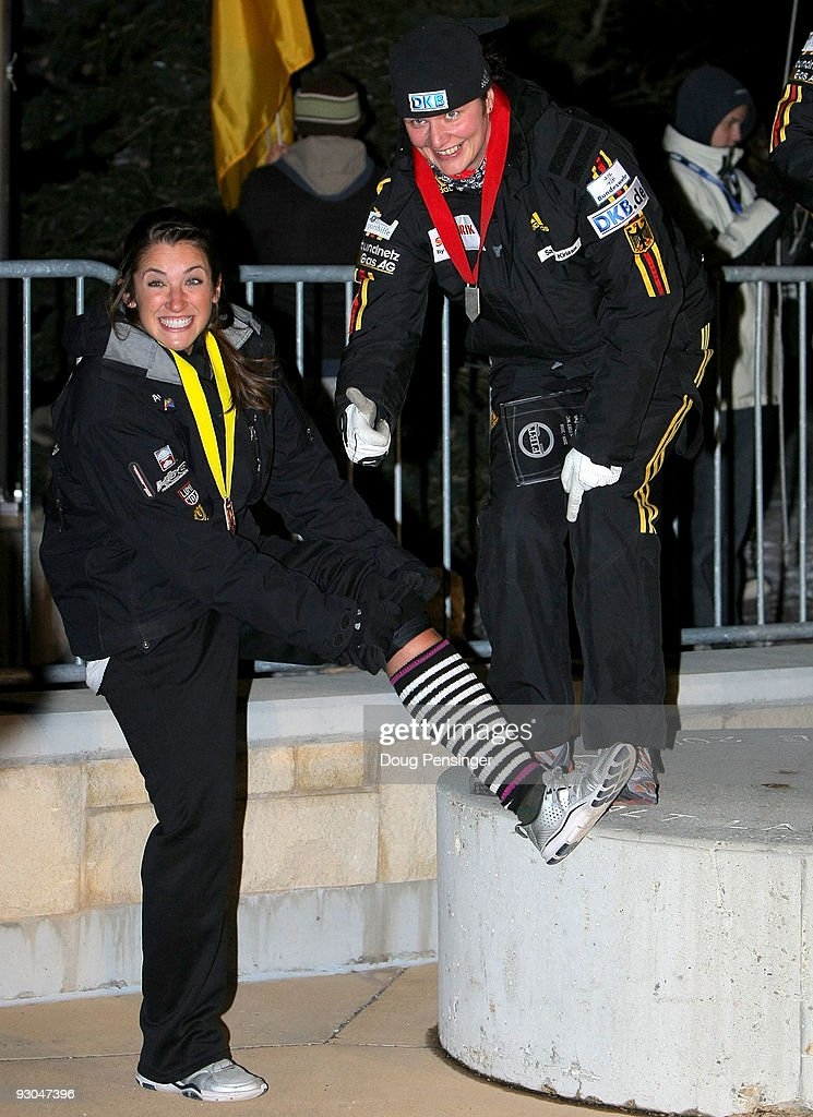 It was a cold night on the podium as pilot Sandra Kiriasis of Germany second place gives a thumbs up to the socks of Bree Schaaf of the USA fourth...