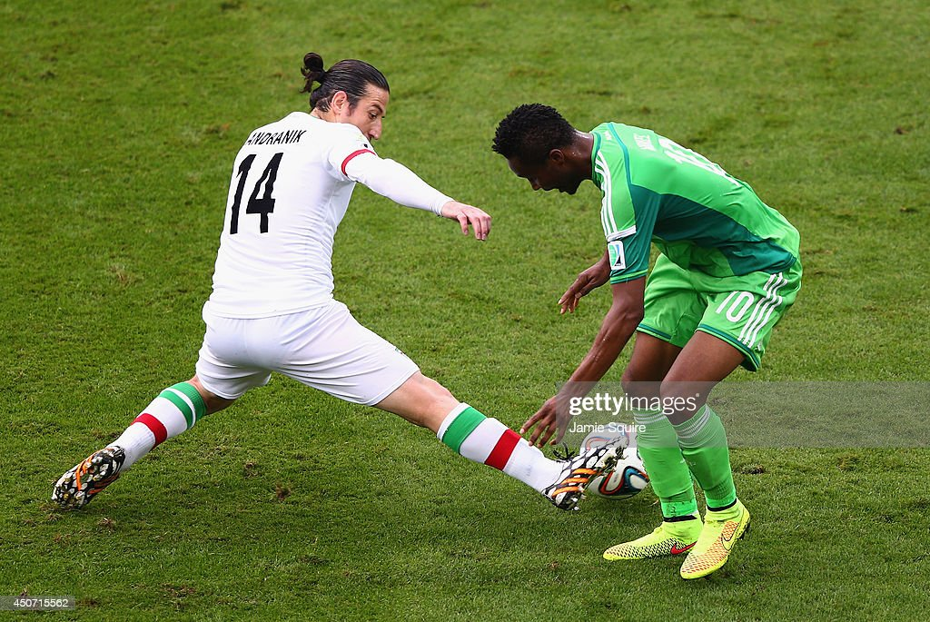 ita14 challenges John Obi Mikel of Nigeria during the 2014 FIFA World Cup Brazil Group F match between Iran and Nigeria at Arena da Baixada on June 16, 2014 in Curitiba, Brazil.