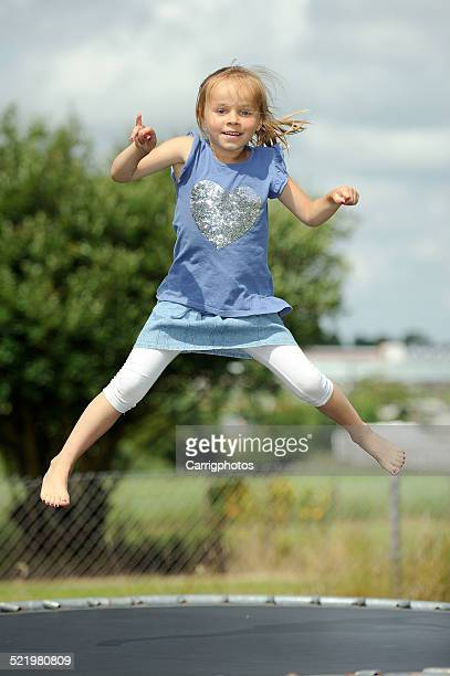 Italia, Calabria, Girl (2-3) jumping on trampoline in summer