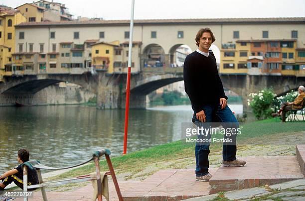 Italian actor Alessandro Preziosi posing on a staircase leading to the Arno River In the background the Ponte Vecchio seen from Santa Trinita Bridge...