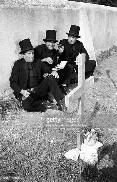 Italian actor and comedian Walter Chiari in the middle with Italian actors Ugo Tognazzi and Raimondo Vianello dressed in black wearing a top hat in a...