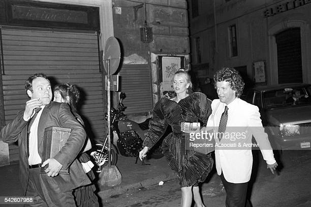 Italian actor and director Carlo Verdone and Italian producer Vittorio Cecchi Gori with his wife Rita Rusic in the street by night coming out of a...