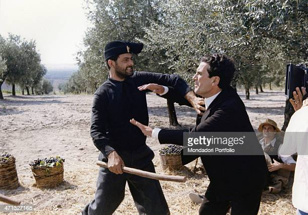 Italian actor and director Massimo Troisi fighting with a man in an oliveyard the film Le vie del Signore sono finite 1987