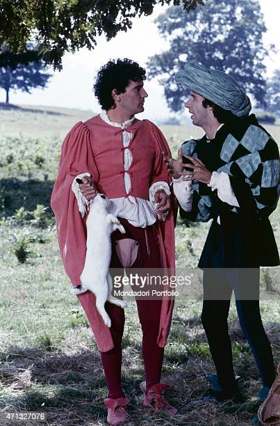 Italian actor and director Massimo Troisi holding a rabbit by the ears beside Italian actor and director Roberto Benigni in the film Non ci resta che...